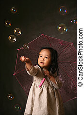 Soap bubbles - The small Korean girl with a umbrella and...