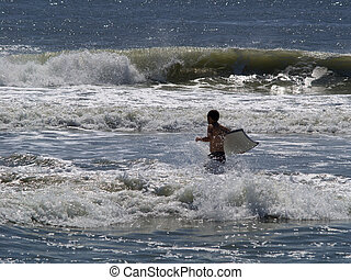 Body Boarding - Young man wading out into the surf to go...