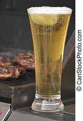 Beer and Burgers - Cold beer set against burgers grilling on...