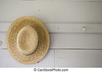 One Hat Hanging - Close Up of A Straw Hat Hung On A Peg