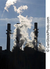Power plant 1 - Backlit smoke stacks of a coal-burning power...
