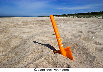 Beach spade - Orange plastic spade in the sandy seashore