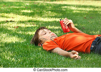 Stock Photo of Boy in park listening to mp3 player - a young boy ...