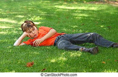 Boy in park listening to mp3 player