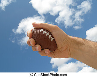 No Stress - Hand holding a stress rubgy ball on a cloudy sky