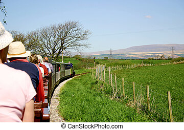 narrow gauge passenger train filled with tourists travelling...