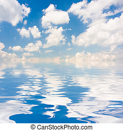 Blue Sky - Blue sky with fluffy clouds reflected on water...
