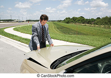 Businessman Checking Under Hood - A businessman with car...