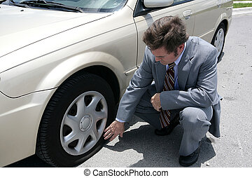Flat Tire - A man dressed for a business meeting discovering...