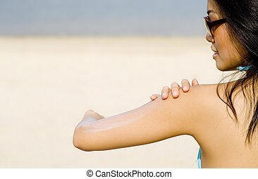 Applying Suncream At Beach - A young Asian woman applying...