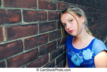 Girl upset - Young girl near brick wall looking upset