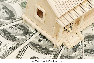 Home and money - wooden house and cash,focus point on...