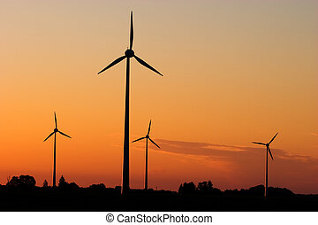 Wind generators in sunrise - Four windturbines against...