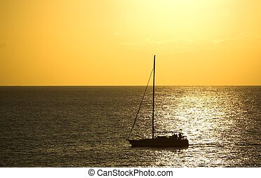 Sunset and a Boat - A silhouette of a sailing boat crossing...