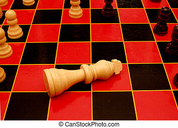 The king is dead. - King piece on a chess board in the draw...