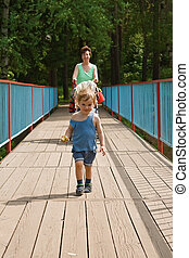 Happy mother and child go on the bridge forward