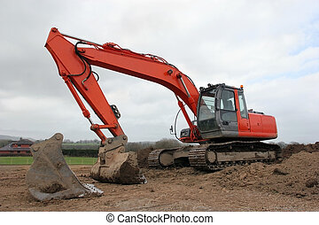 Earthmover - Large orange digger standing idle on muddy...