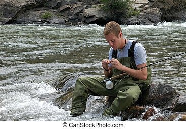 Stream Fishing - A fisherman in a stream baiting his hook