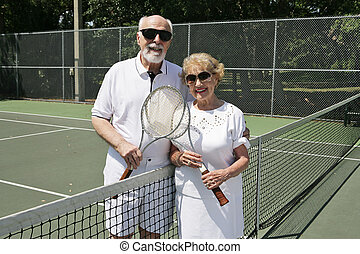 On the Tennis Court - An active senior couple in sunglasses...
