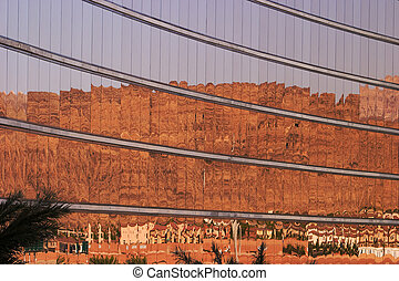 Desert Mountain Reflections - Gold-tinted windows on the...
