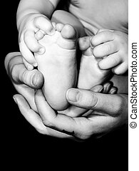 Baby Feet - An infants feet being held in the loving hands...