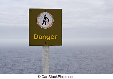 Danger - A weathered sign along the cliff face at cape spear