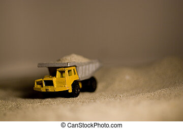 Dump Truck - A closeup of a toy dumptruck in sand