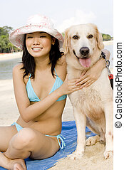 Girl With Dog At Beach - A young attractive Asian woman...
