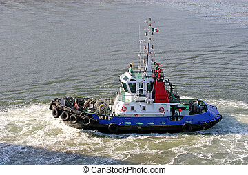 Tug in Motion - A tugboat moving through the water at a port