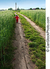 To the cross - Little girl going towards the field cross