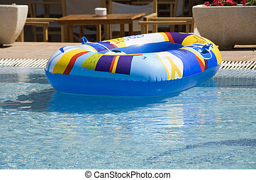 Holiday - An inflatable dinghy floats in a swimming pool