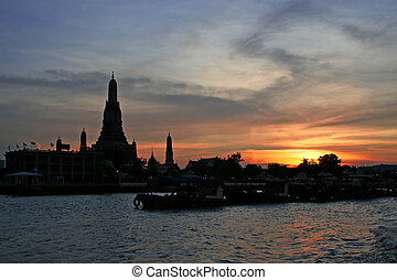 Wat Arun Thailand - Boats pass in front of Wat Arun on the...