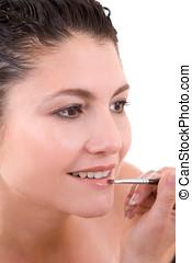 Applying lipgloss - Pretty brunette applying lipstick to her...