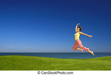 Young woman jumping - Beautiful woman jumping on a green...