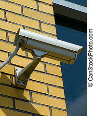 Security camera - white security camera on the yellow brick...