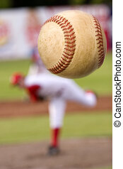 The pitch - A baseball player pitching with spin on the...