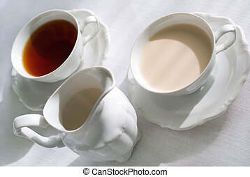 Two cups of tea and milk jug. - Two cups of tea (one with...