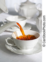 Pouring fresh tea. - Pouring fresh tea from porcelain tea...