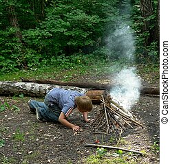 boy kindles bonfire in the deciduous forest