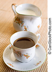 Coffee cup and the milk jug - Cup of coffee or black tea on...
