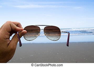 Sunglasses - Handhold Sunglasses in front of a beach....