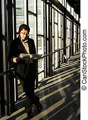 Reading businessman - A businessman reading a newspaper in a...