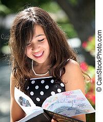 Happy girl with a book - Happy girl reading a book on a...