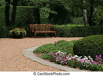 Bench in garden - A wooden bench in the garden surrounded by...