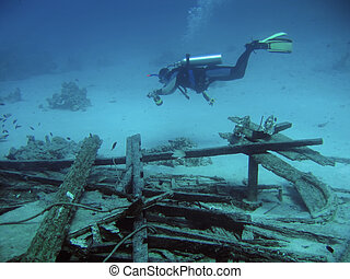 diver in deep and wreck of ship