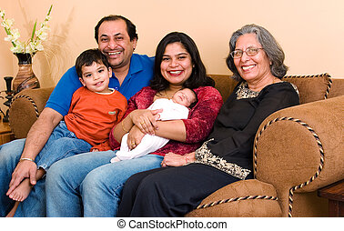 East Indian family at home - An East-Indian family sits in...
