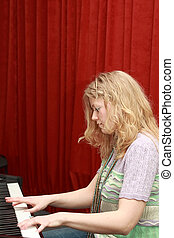Woman playing piano - Young blonde woman playing piano...