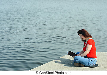 On sea embankment - Woman in jeans and red shirt sitting and...