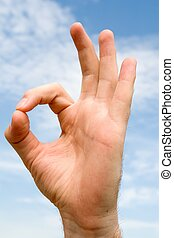 OK` hand gesture with blue sky at background