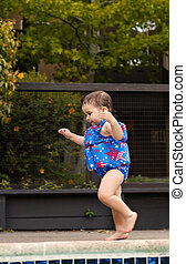 Infant girl running by the pool 1 - A toddler girl is...